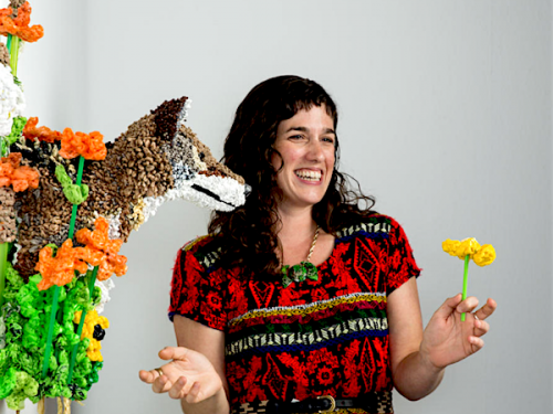 brunette woman in red patterned dress standing to the right of bust sculpture of fox made of plastic