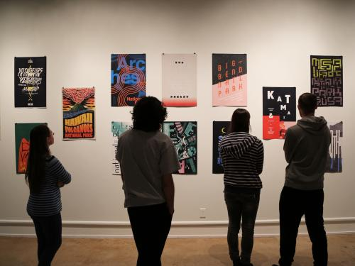 silhouettes of visitors in front of poster prints