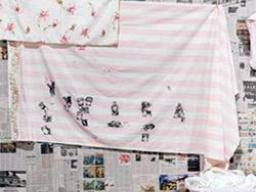 an image of black ink block artwork on a sheet, hanging on a laundry line