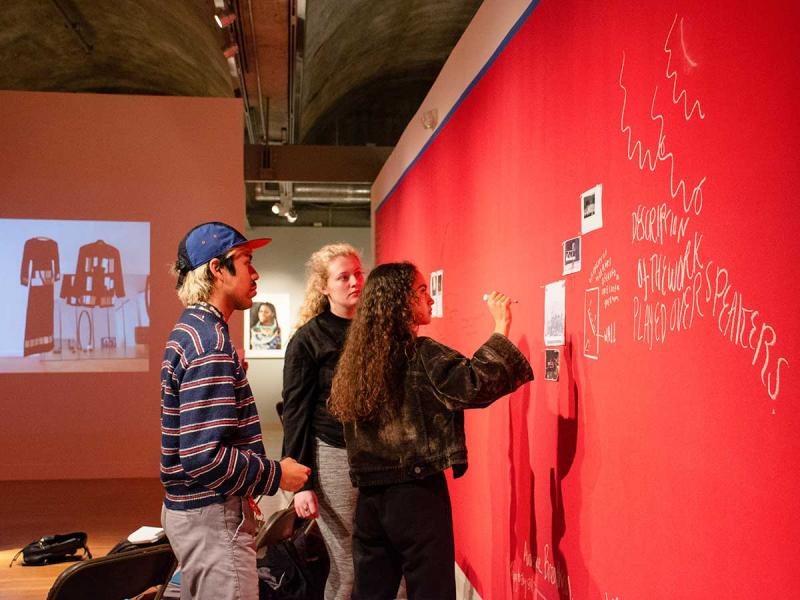 students discussing exhibition installation